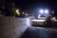 Los operarios trabajan de noche para arreglar el pavimento